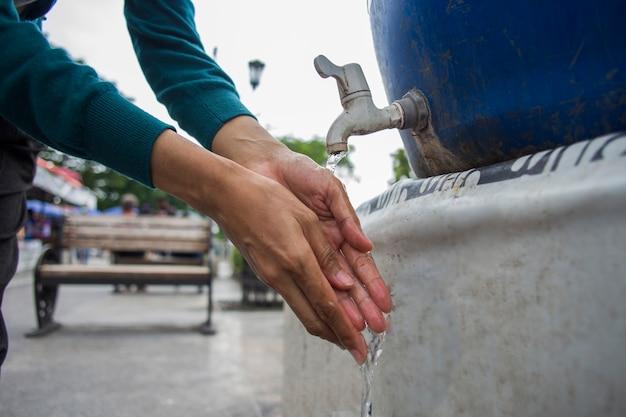 Gros plan d'une femme se lavant les mains dans l'espace public