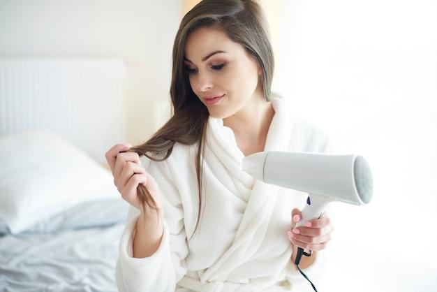 Gros plan de femme avec sèche-cheveux