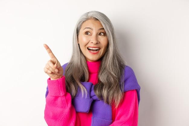 Gros plan d'une femme senior coréenne élégante aux cheveux gris regardant et pointant vers le coin supérieur gauche, montrant l'offre de promotion, debout sur fond blanc.