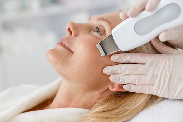 Gros plan femme senior dans un salon de beauté professionnel au cours de la procédure de nettoyage du visage par ultrasons.