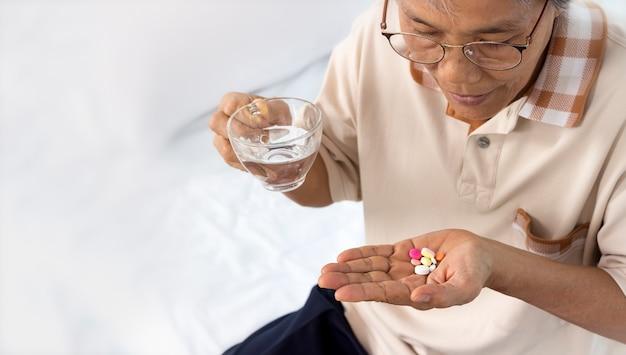 Gros plan d'une femme senior avec des pilules et un verre d'eau à la maison
