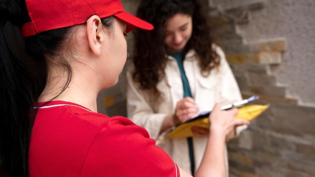 Gros plan femme signant un document pour la livraison