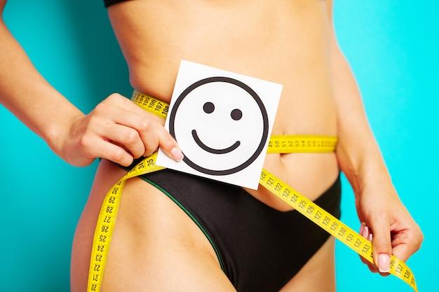 Gros plan d'une femme avec une silhouette élancée montre le résultat tenant une carte près de son estomac avec un sourire souriant et du ruban à mesurer jaune.