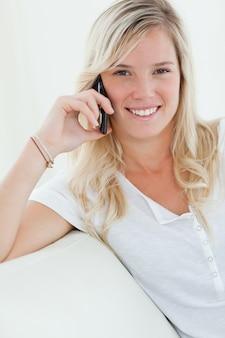 Gros plan d'une femme souriante alors qu'elle parle au téléphone