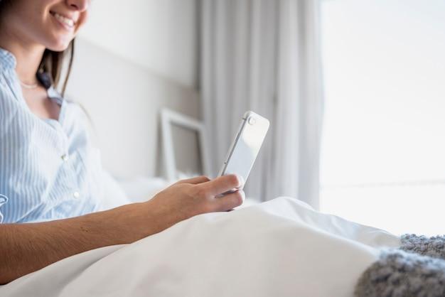 Gros plan de femme souriante assise sur le lit à l'aide de tablette numérique