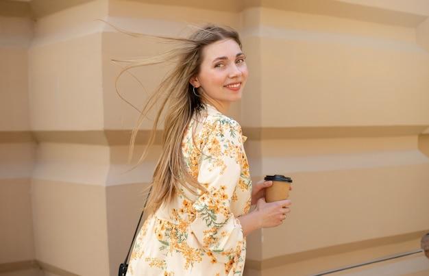 Gros plan d'une femme souriante aux cheveux blonds flottant dans une robe buvant du café à emporter sur fond de mur beige