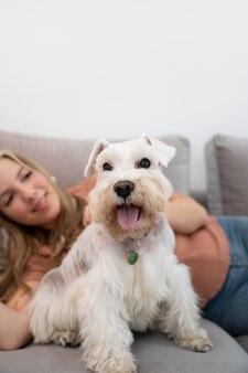 Gros plan femme souriante et chien sur canapé