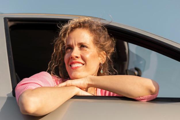 Gros plan, femme souriante, dans voiture