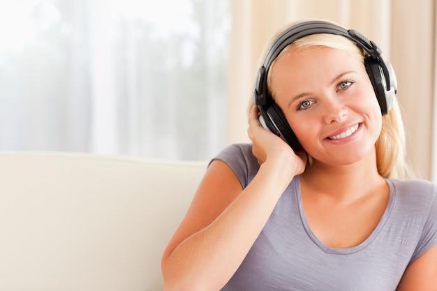 Gros plan d'une femme souriante, écoutant de la musique