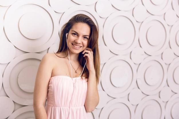 Gros plan de femme souriante, écouter de la musique avec des écouteurs