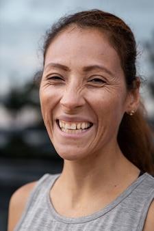 Gros plan femme souriante à l'extérieur