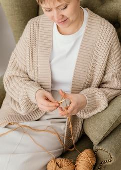 Gros plan, femme souriante, sur, fauteuil, tricot
