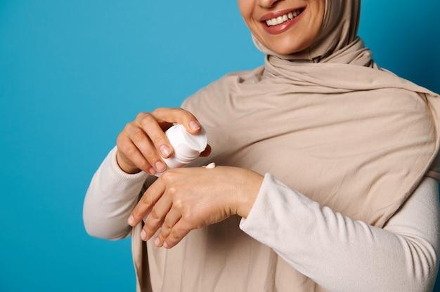 Gros plan de femme souriante en hijab pressant la crème sur place, isolé