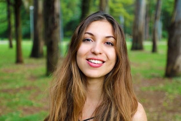 Gros plan d'une femme souriante naturelle en plein air dans le parc