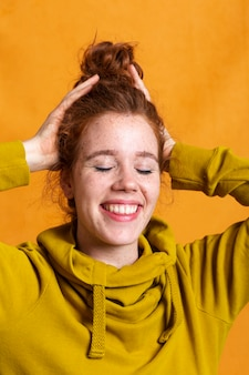 Gros plan femme souriante posant avec capuche jaune