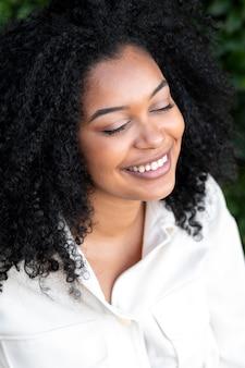 Gros plan femme souriante posant à l'extérieur