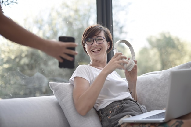 Gros plan d'une femme souriante regardant un téléphone dans les mains d'une personne