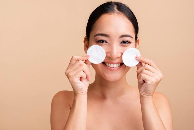 Gros plan femme souriante avec des tampons de coton