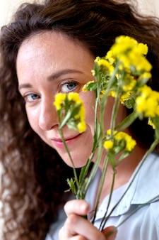 Gros plan femme souriante tenant des fleurs
