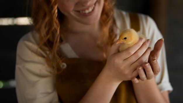 Gros plan, femme souriante, tenue, poulet