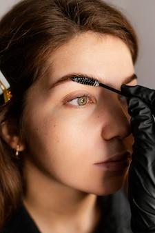 Gros plan d'une femme spécialiste faisant un traitement des sourcils pour femme