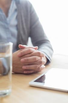 Gros plan de femme à table avec de l'eau et une tablette
