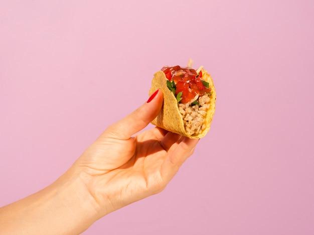 Gros plan femme avec taco et fond rose