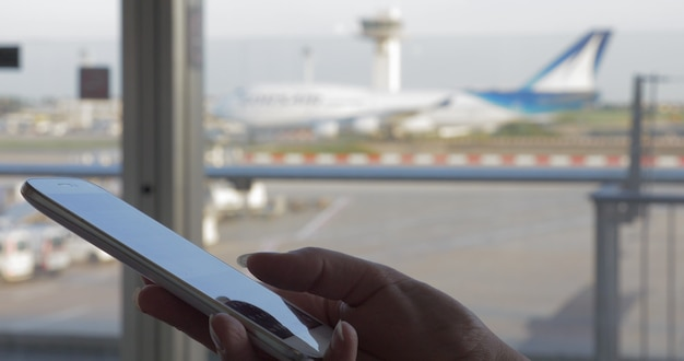 Gros plan d'une femme tapant des sms sur un téléphone intelligent près de la fenêtre du terminal de l'aéroport avec vue sur l'avion en mouvement