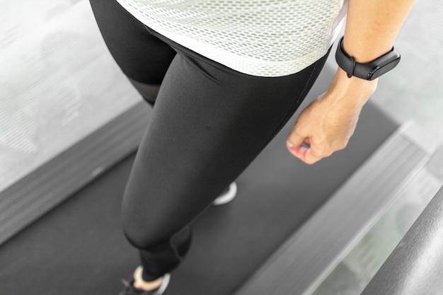 Gros plan de femme sur tapis roulant. concept de partie du corps de la femme et entraînement.