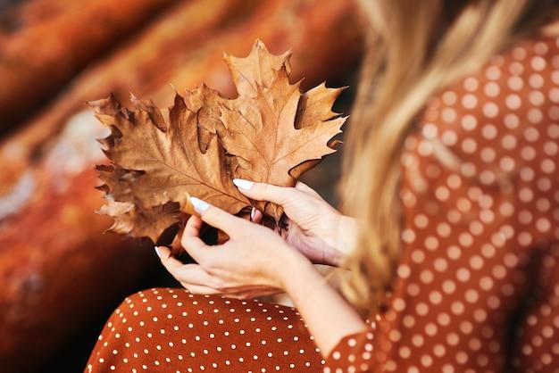 Gros plan d'une femme avec un tas de feuilles d'automne