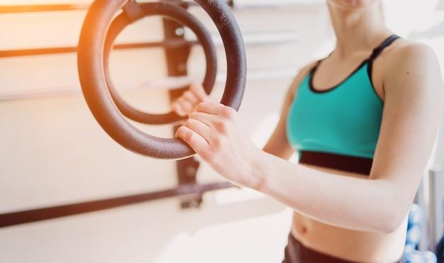 Gros plan femme tenant des anneaux de gymnastique dans la salle de gym
