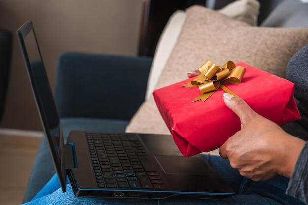 Gros plan d'une femme tenant une boîte-cadeau rouge en face de son ordinateur portable