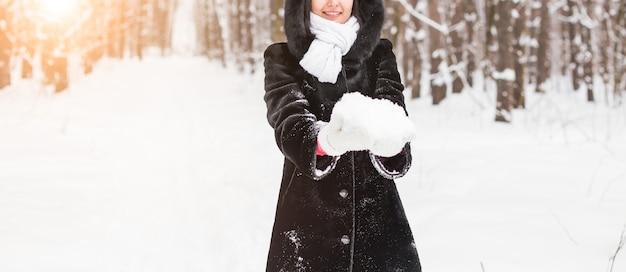 Gros plan d'une femme tenant la boule de neige dans les mains, concept d'hiver avec espace de copie.