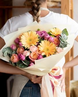 Gros plan femme tenant un bouquet de fleurs
