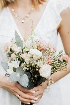 Gros plan d'une femme tenant un bouquet de fleurs