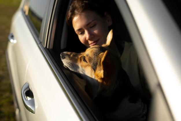 Gros plan femme tenant un chien en voiture