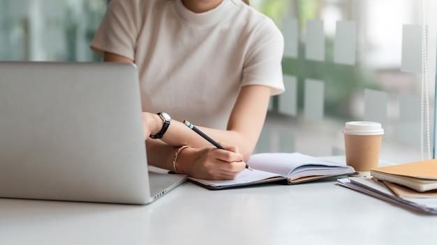 Gros plan d'une femme tenant un crayon et prenant des notes au bureau.
