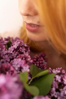 Gros plan femme tenant des fleurs