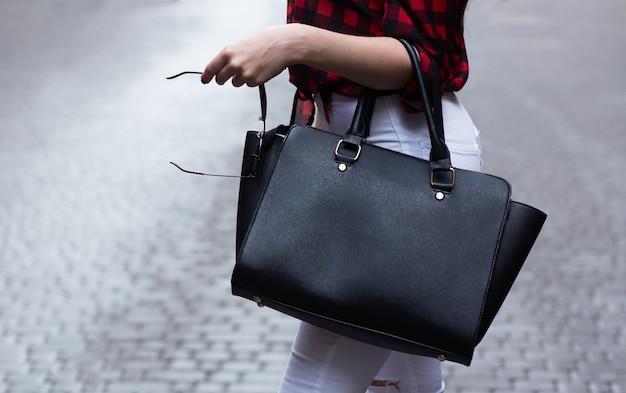 Gros plan d'une femme tenant un gros sac à main en cuir noir. espace pour le texte