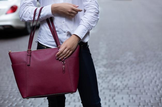 Gros plan d'une femme tenant un gros sac à main en cuir rouge. espace libre