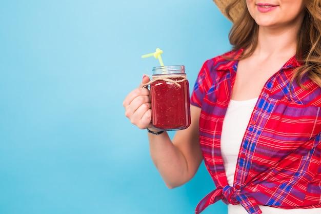 Gros plan d'une femme tenant un jus de fruit ou un cocktail sur fond bleu et espace de copie