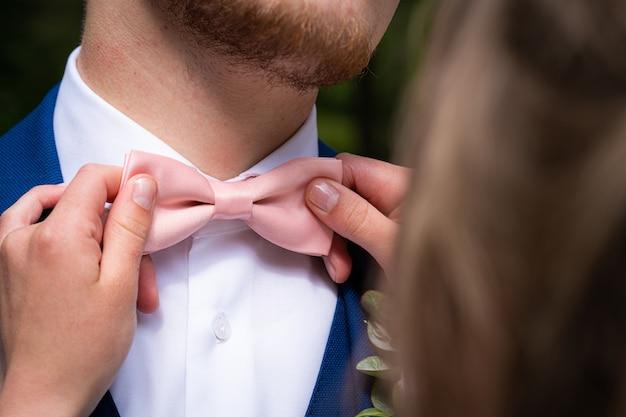 Gros plan d'une femme tenant le noeud papillon rose du mâle