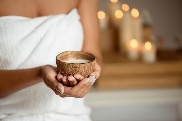 Gros plan de femme tenant la noix de coco dans le salon spa.
