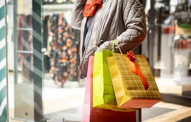 Gros plan d'une femme tenant des sacs à provisions en regardant la vitrine