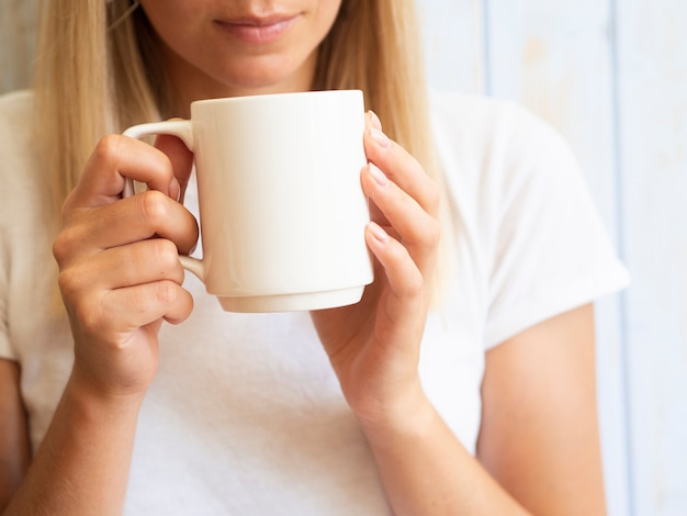 Gros plan femme tenant une tasse blanche