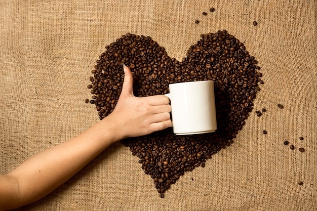 Gros plan d'une femme tenant une tasse contre le coeur fait de grains de café