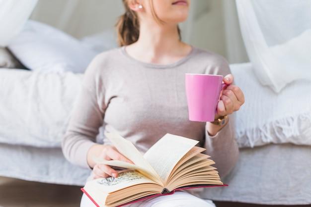 Gros plan, femme, tenue, café, tasse, livre