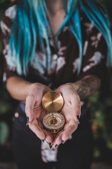 Gros plan, femme, tenue, doré, vintage, compas, main