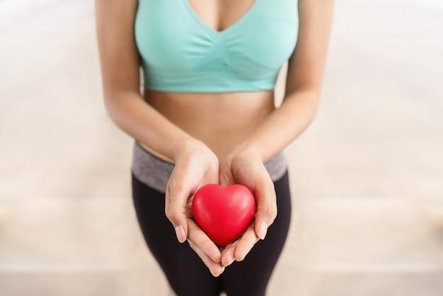 Gros plan, femme, tenue, rouge, coeur, mains