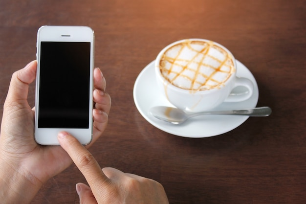 Gros plan, de, femme, tenue, téléphone portable, à, tasse café, sur, bureau, dans, café